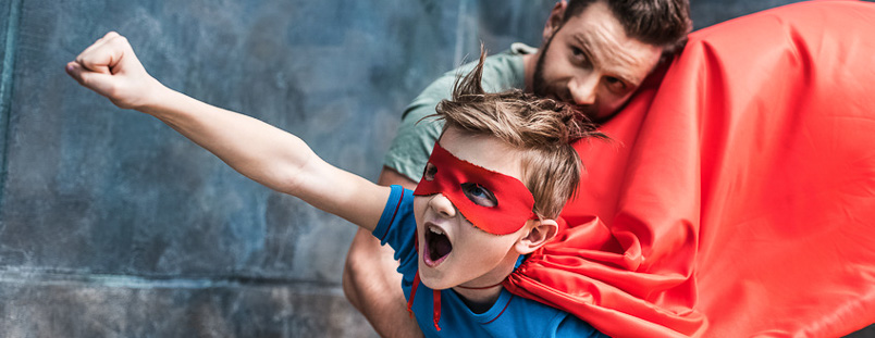 father holding son in superhero costume flying at home